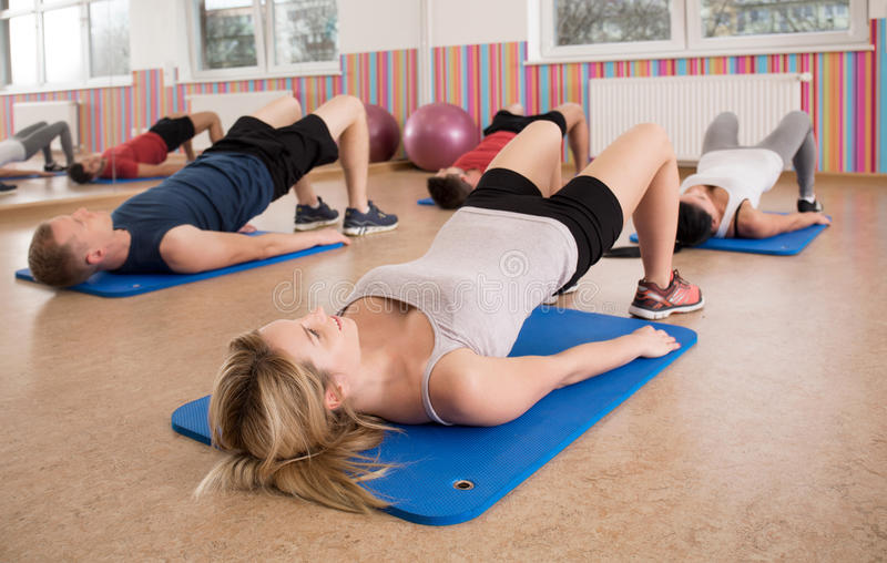 Exercice sur des tapis de plancher de gymnase image stock
