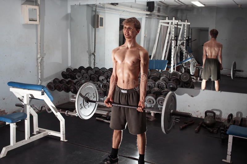 Exercice sur le biceps avec le barbell Un jeune homme sportif maigre exécute photo libre de droits