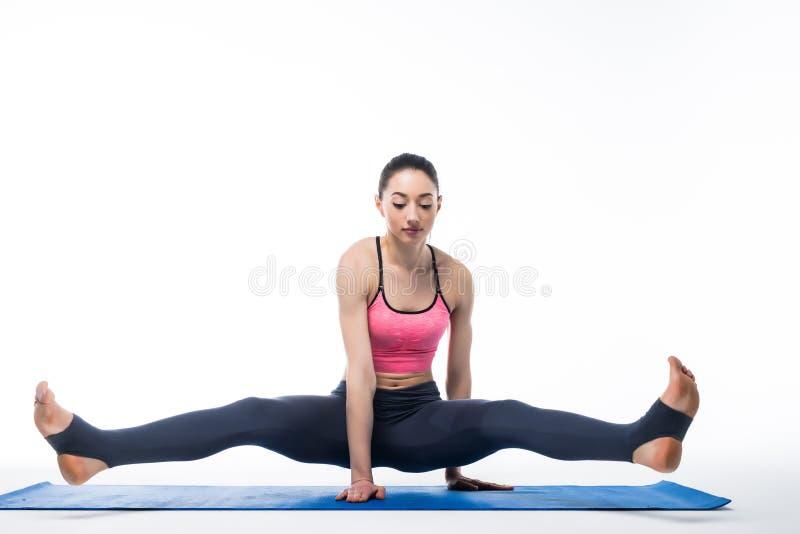 Exercice travaillant de yoga de jeune femme de beauté d'isolement sur le fond blanc photographie stock libre de droits