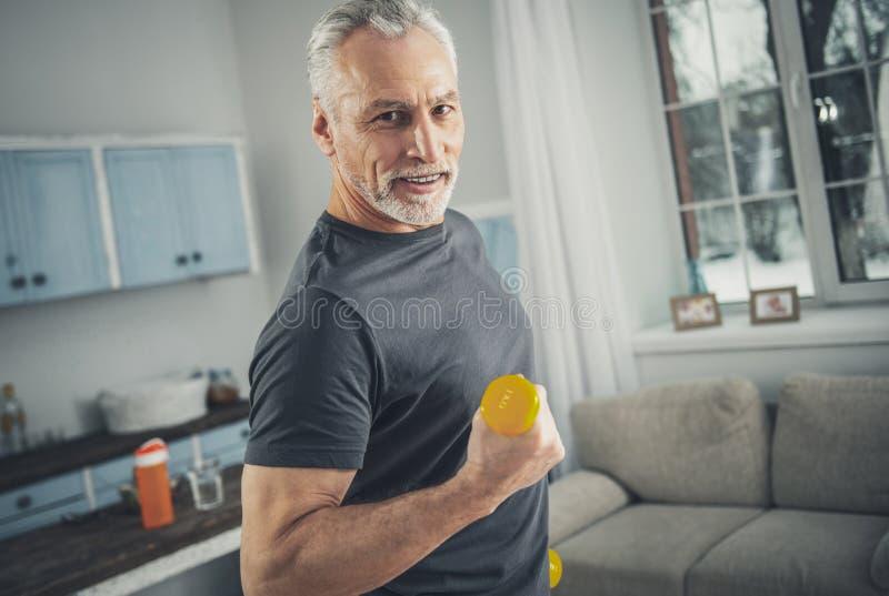 Exercices aimants de sport d'homme plus âgé aux cheveux gris image stock