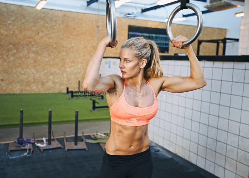 Exercices convenables de jeune femme avec des anneaux de gymnaste image libre de droits