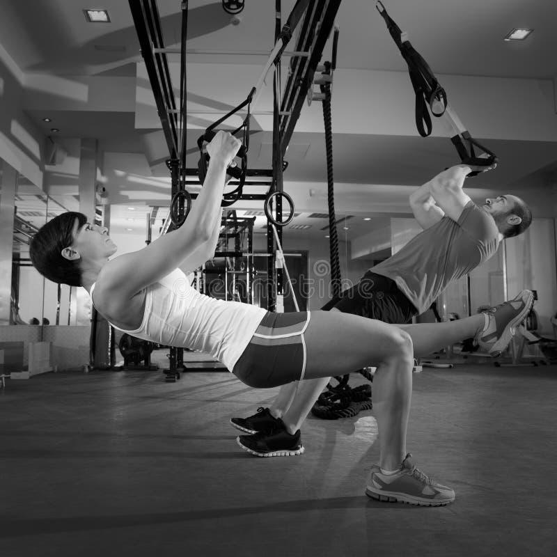 Exercices d'entraînement de la forme physique TRX à la femme et à l'homme de gymnase photo libre de droits