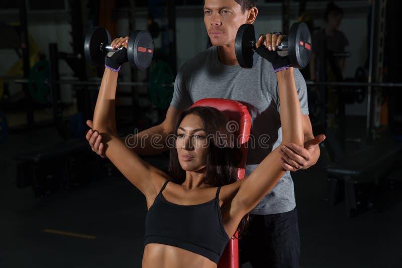 Exercices de couples avec des haltères ensemble dans le gymnase photographie stock libre de droits