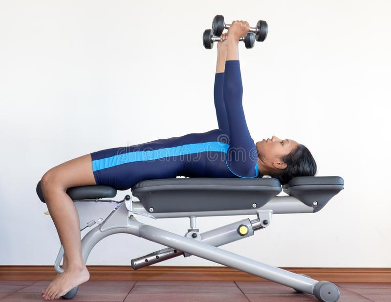 Exercices de femme avec des haltères dans le gymnase photo libre de droits