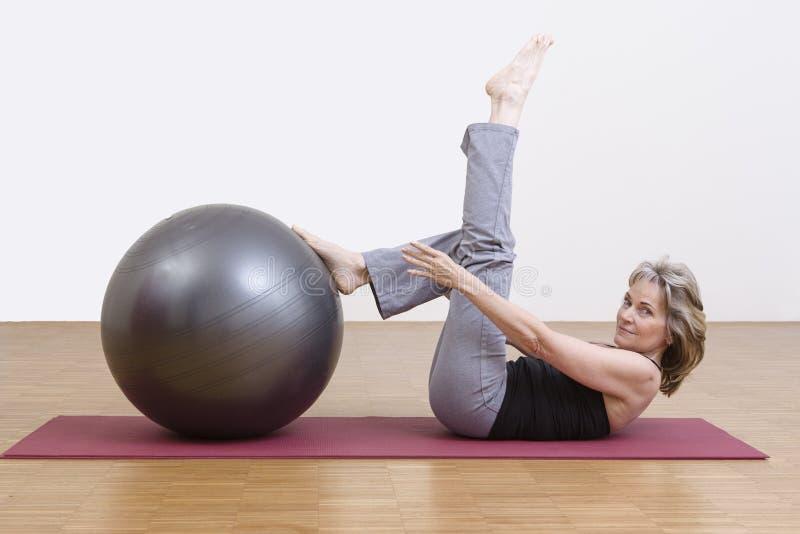 Exercices de femme avec la boule de pilates photo stock