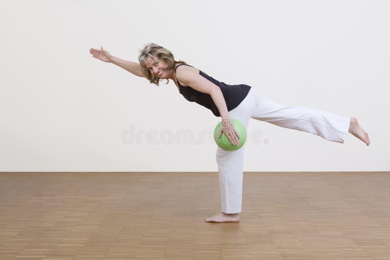 Exercices de femme avec la boule verte image libre de droits