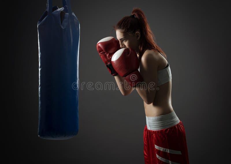 Exercices de femme de boxe avec le sac de sable image stock