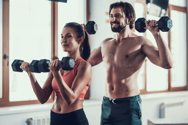 Exercices de fille et de Guy In Gym Doing Dumbbells image stock