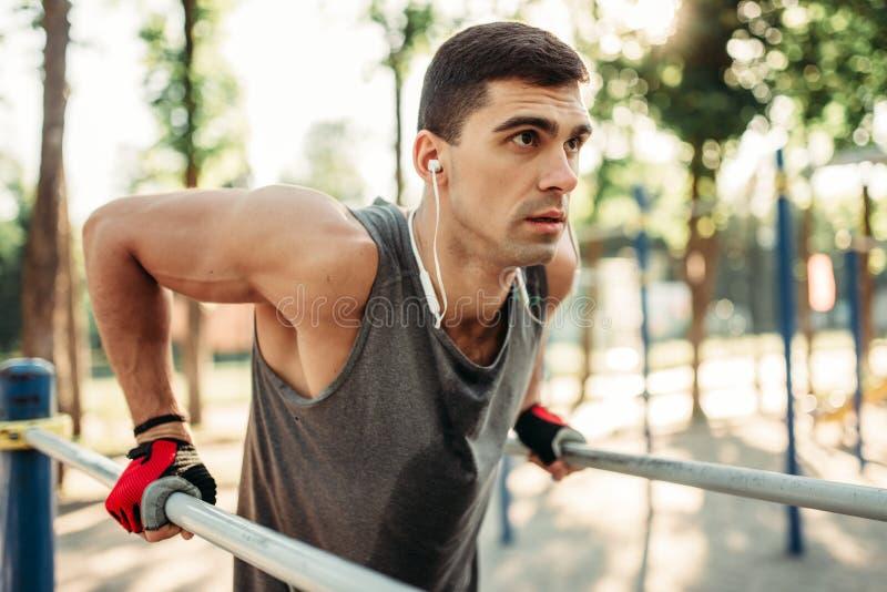 Exercices masculins d'athlète sur des barres parallèles extérieures photographie stock