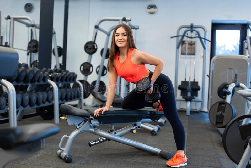 Exercis magros da mulher com pesos no banco no gym fotos de stock