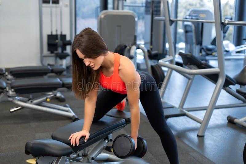 Exercis magros da mulher com pesos no banco no gym fotografia de stock royalty free