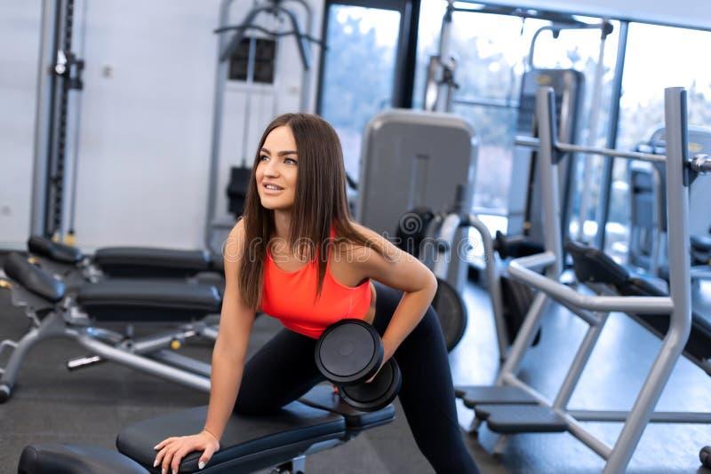 Exercis magros da mulher com pesos no banco no gym foto de stock