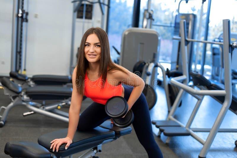 Exercis magros da mulher com pesos no banco no gym imagens de stock