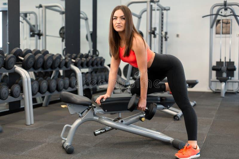 Exercis magros da mulher com pesos no banco no gym foto de stock royalty free