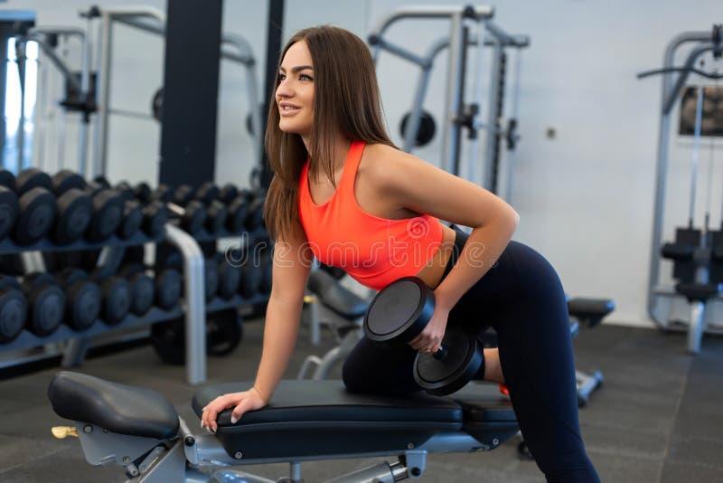 Exercis magros da mulher com pesos no banco no gym imagem de stock royalty free