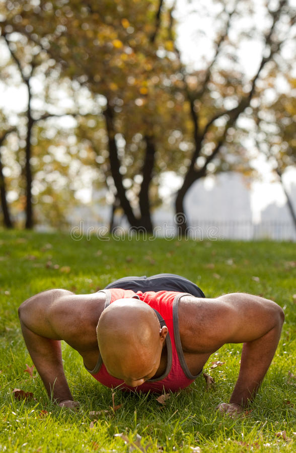 Exercise. An african american male doing push ups in a park royalty free stock images
