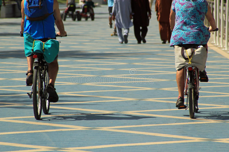 Exercise for all ages. In the foreground are two older cyclists, one with a rucksack and the other with a bag tied on the bag of his bike. In the background are royalty free stock images