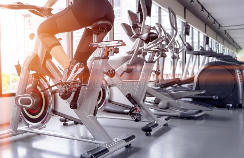 Exercise bike cardio workout at fitness gym. Of woman taking weight loss with machine aerobic for slim and firm healthy in the morning royalty free stock photography