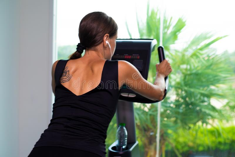 Exercise bike cardio workout at fitness gym of woman taking weight loss. female listens to music on headphones. Athlete stock photography