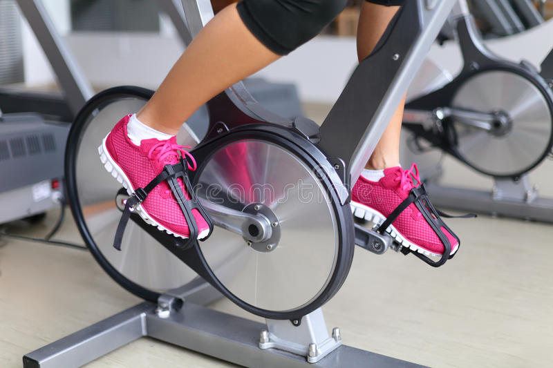 Exercise bike with spinning wheels - woman biking. Exercise bike with spinning wheels. Woman excising biking in fitness center. closeup of pedals. Professional stock image