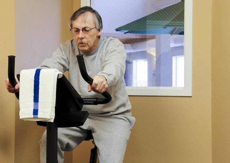 Exercise bike workout. Man working out on an exercise bike in the gym stock images