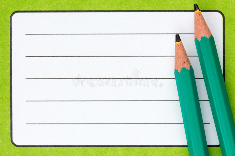 Exercise book name label and pencils. Close up of school exercise book, with name label and pencils royalty free stock photography