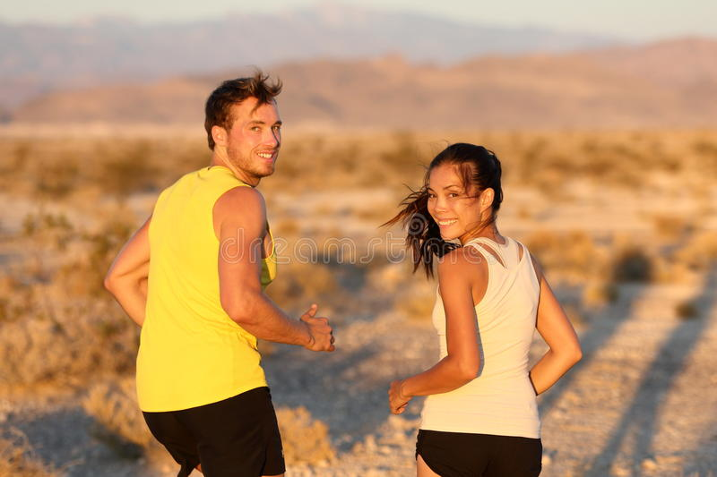 Exercise - couple running looking happy. At camera. Runners jogging outside in cross-country trail run. Fit young athlete men and women fitness runner training stock photo
