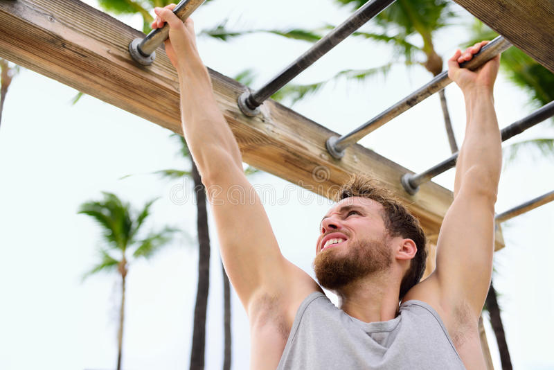 Exercise fitness athlete exercising on monkey bars. Crossfit man working out arms swinging on brachiation ladder as strength training crossfit routine royalty free stock images