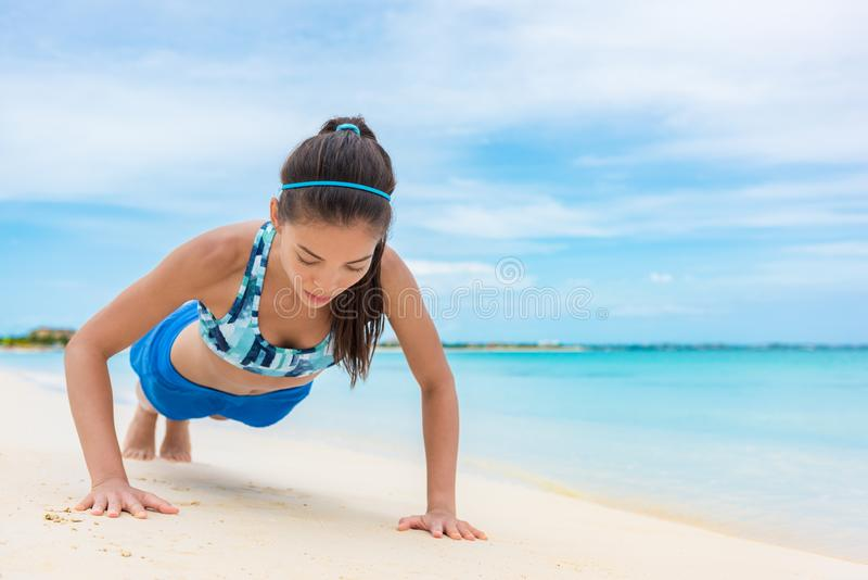 Exercise fitness push up training girl doing bodyweight workout on beach. Asian woman fit active lifestyle. Exercise fitness push up training girl doing stock images