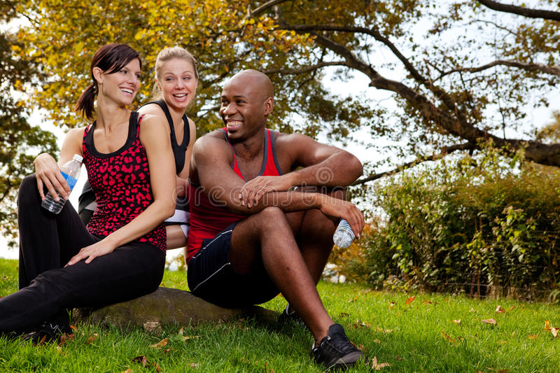 Exercise Group. A group of young adults resting after exercise in the park stock images