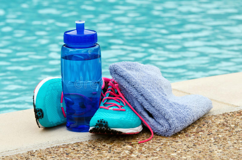 Exercise and hydration concept. Blue water bottle with running shoes and towel by pool. Exercise and hydration concept. Copy space stock images