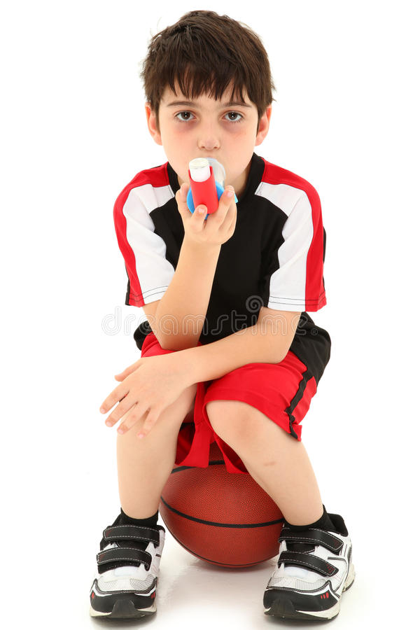 Exercise Induced Asthma. Boy Child with exercise or sport induced asthma attack sitting on basketball over white royalty free stock images
