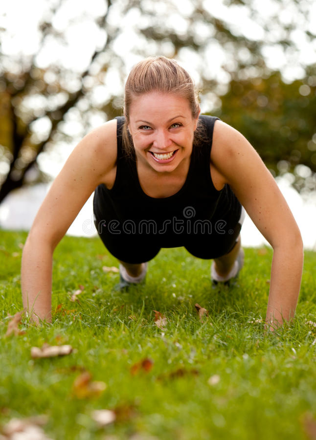 Exercise Park. A woman doing push-ups in the park stock photo