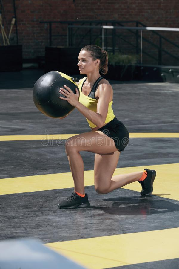 Exercise. Sport woman doing leg workout with med ball outdoors. Fitness girl with fit body exercising, doing lunge training with medicine ball on street stock images