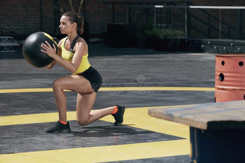 Exercise. Sport woman doing leg workout with med ball outdoors. Fitness girl with fit body exercising, doing lunge training with medicine ball on street royalty free stock photography