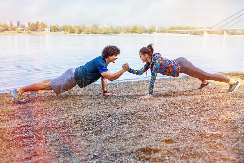 Exercise - Sportswoman and sportsman giving high five to each other while doing push ups stock photography
