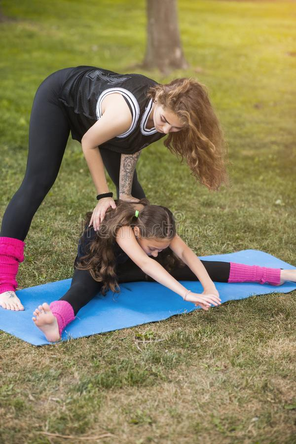 Exercise for stretching. Active teenage sport. Family teamwork gymnastics with coach, healthy beautiful lifestyle. Nature background, creative and fun royalty free stock images