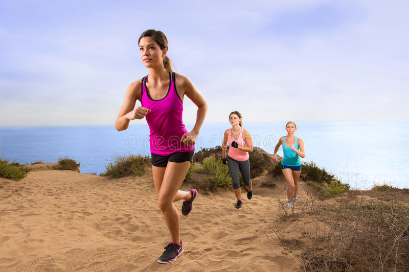 Exercise team fitness group jogging running hiking up hill trail path in nature. Outdoors near ocean beach california mountain top stock photos