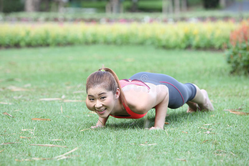 Exercise woman doing push ups in outdoor workout training. Asian. Photo of Exercise woman doing push ups in outdoor workout training. Asian sport fitness woman stock images