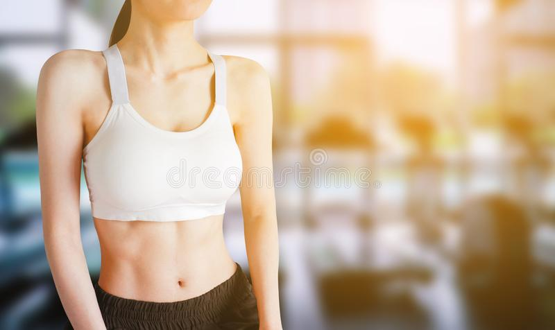 Exercise Workout. Young Woman Wearing White Sport Bra and Pants with Muscular Body and Strong Six Pack Abs in Gym Fitness. Sexy stock photography