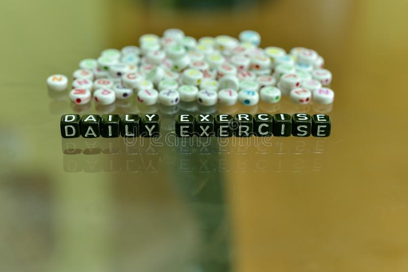 DAILY EXERCISE  written with Acrylic Black cube with white Alphabet Beads on the Glass Background.  stock photos