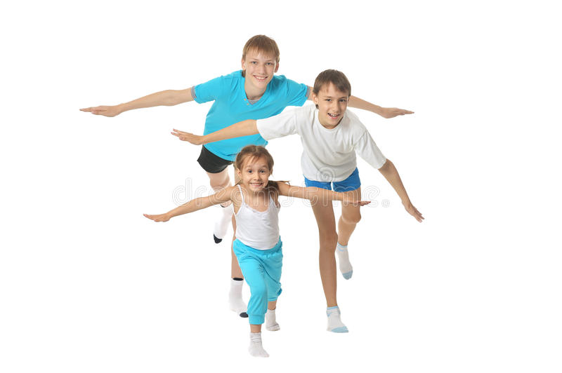 Exercising children. Two young boys brothers and little sister exercising isolated on white background royalty free stock photos