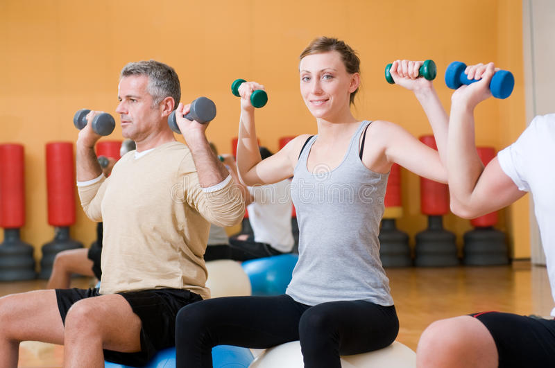 Exercising with fitness ball at gym. Young lady smiling and looking at camera while lifting weigths on a fitness ball at gym royalty free stock photography