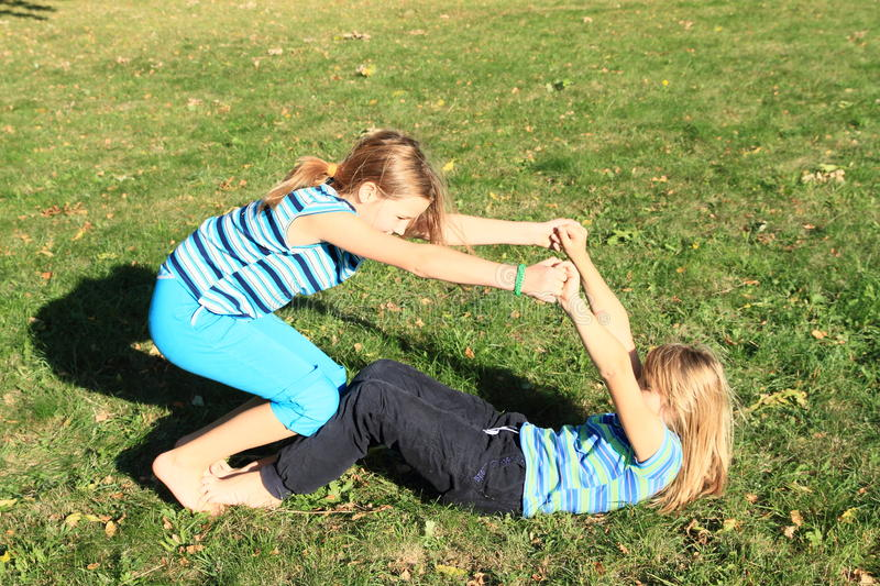 Exercising girls. Two barefoot girls - young kids in t-shirt with stripes exercising yoga - getting ready for flying on feet on green meadow stock images
