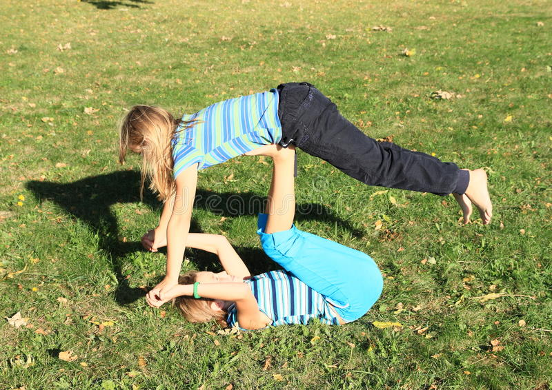 Exercising girls. Two barefoot girls - young kids in t-shirt with stripes exercising yoga - one flying on feet of the second one on green meadow royalty free stock images