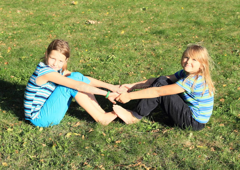 Exercising girls. Two smiling barefoot girls - young kids in t-shirt with stripes exercising yoga - holding hands and feet on green meadow royalty free stock images