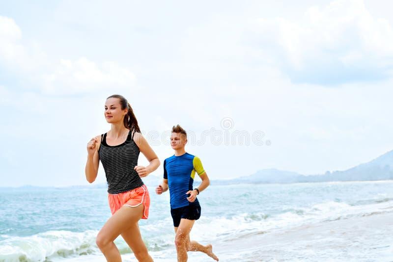 exercising Pares felices que se ejecutan en la playa Deportes, aptitud cure fotografía de archivo libre de regalías