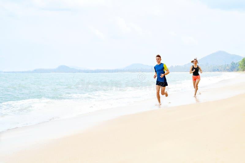 exercising Pares felices que se ejecutan en la playa Deportes, aptitud cure imagenes de archivo