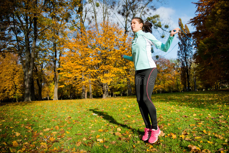 Exercising with skipping rope. Workout - young woman jumping with skipping rope royalty free stock photos