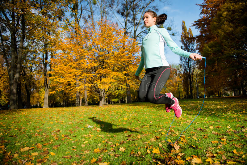 Exercising with skipping rope. Workout - young woman jumping with skipping rope royalty free stock photography